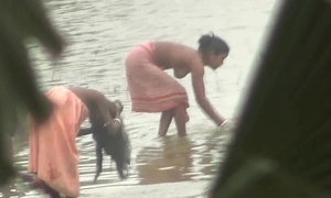 Indian women bathing by hammer away river